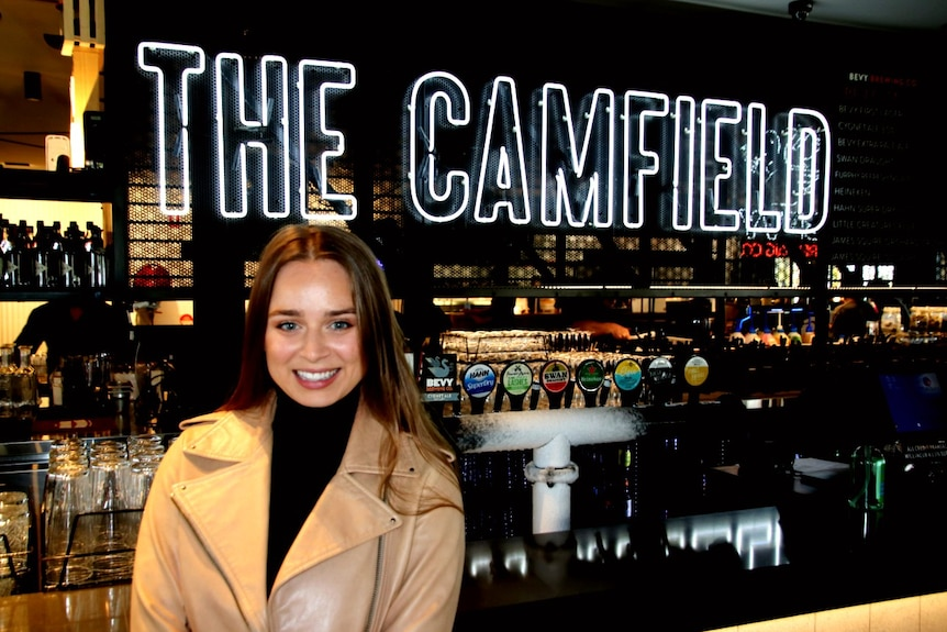 A woman wearing a leather jacket stands in front of the bar of the Camfield in Burswood, in Perth's east.