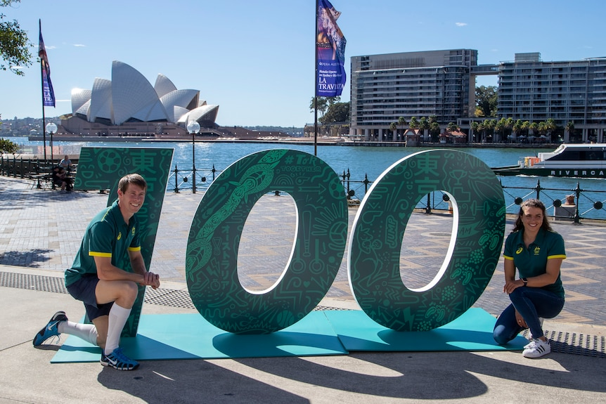 Olympians Edward Fernon and Jess Fox pose on either side of a 100 sign in front of Sydney Harbour.