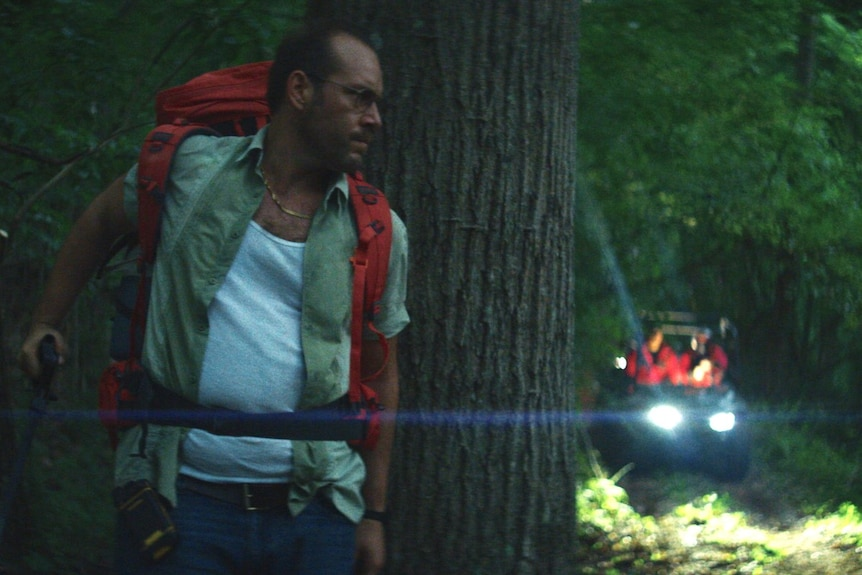 Dean Imperial, a middle aged man with a backpack his back against a tree in a dark night, in the film Lapsis