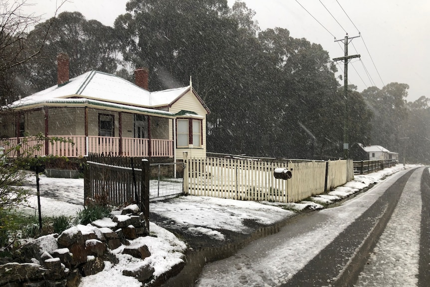 Snow falls on a house