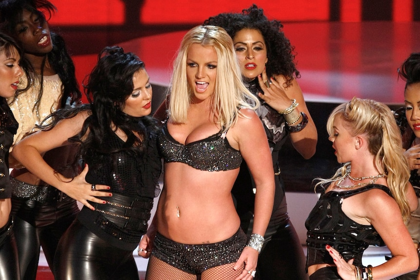 Britney Spears in a black bra and fishnets singing on stage, surrounded by backup dancers
