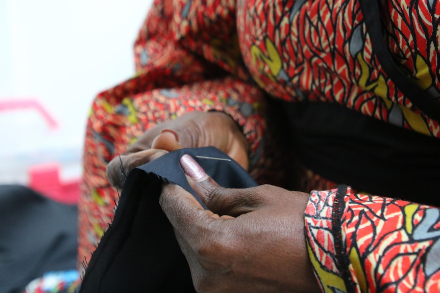 A close-up shot of a woman's hands as she sews with a needle.