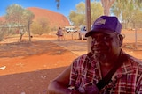 An Aboriginal man sitting in the shade with a cap on with Uluru in the background