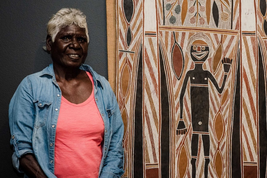Lady standing next to a bark painting.
