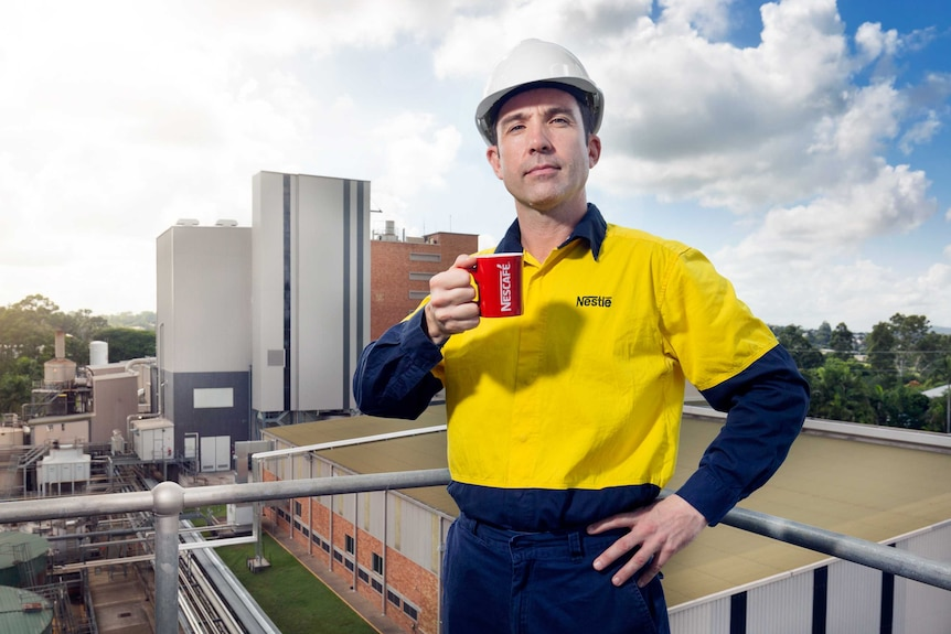 A mid shot of a man in high vis standing on a balcony holding a coffee cup with a factory in the background