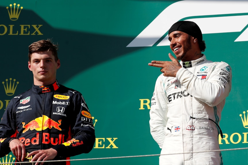 A Formula One driver aims his fingers at an unimpressed rival on the podium after a grand prix race.