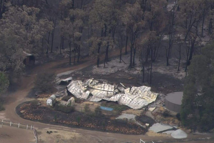 A property that has been flattened by the Wooroloo bushfire is surrounded by burnt trees and scrub.