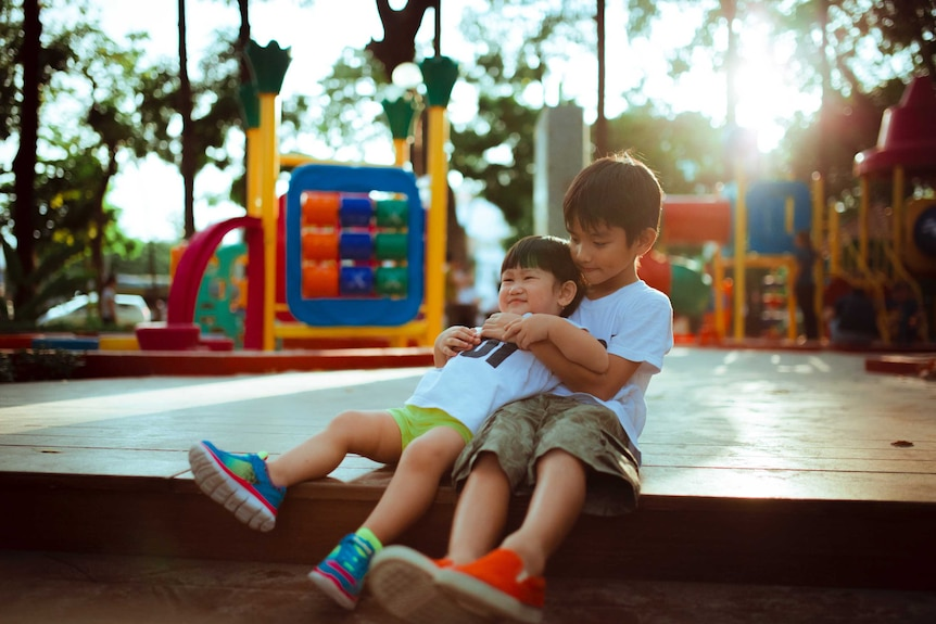 Two young boys sitting at a playground, the older one is holding the younger one