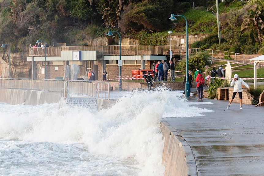 A high tide washes over a walkway on Sydney's coast.