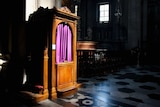 Wooden confession booth with purple curtain, in Catholic church.