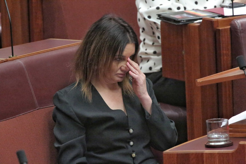 Jacqui Lambie appearing to wipe a tear from her eye while in the Senate