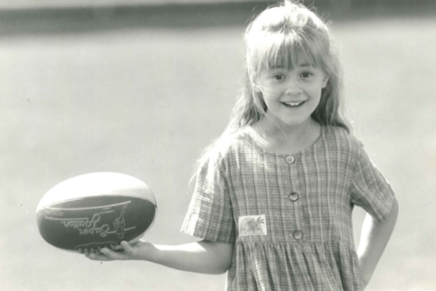 A black-and-white photo of a young girl holding a football
