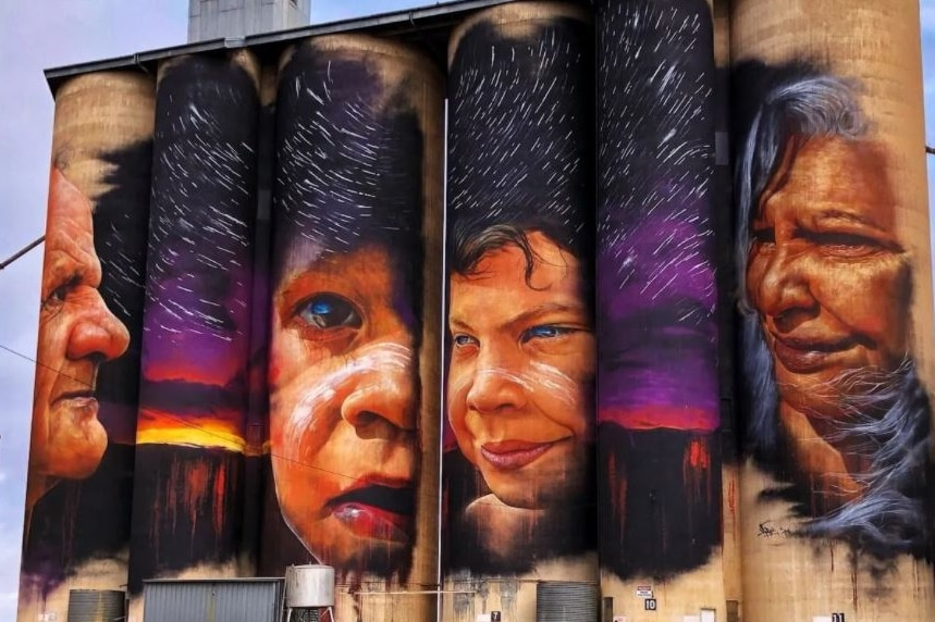 Four grain silos with the faces of four aboriginal people painted in beautiful colours against a stary night sky.