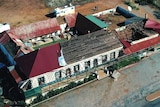 Aerial shot of an old tavern with most of the roof missing and debris laying on the ground nearby.