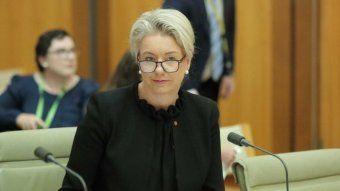 Bridget McKenzie look over her glasses to the camera while sitting in a wood panelled room
