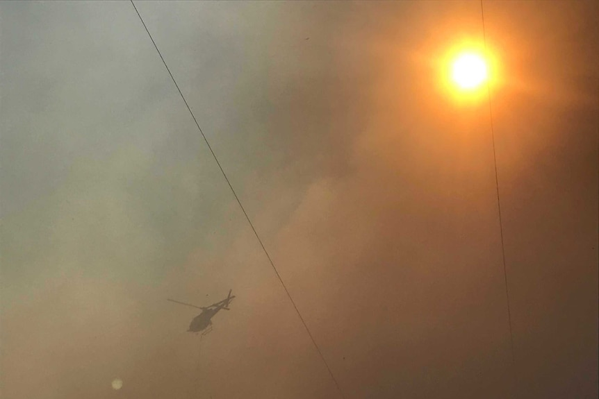 A helicopter flies in smoke-filled air. The sun can be seen shining brightly through the smoke.