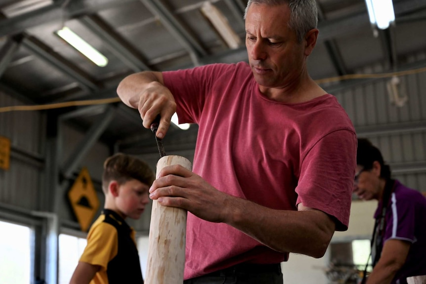 A grey-haired man uses a chisel as he works on a didgeridoo.