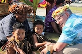 Scott Morrison crouches and smiles next to children who are floating in water.