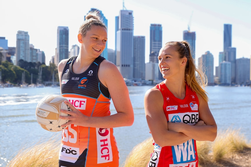 Jo Harten stands tall, holding the Grand Final ball, smiling back-to-back at Paige Hadley, in front of a Brisbane sky line