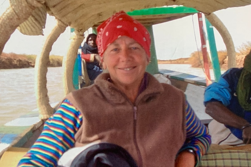 older woman wearing red bandanna with brown vest and colourful stripy shirt smiles at the camera while sitting on boat