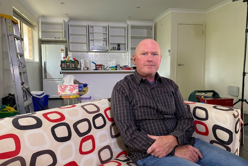 Man sitting on a couch in a unit being packed up with empty cupboards and boxes in the background.