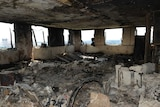 A view inside one of the flats shows all the windows smashed out and everything burnt to ash.