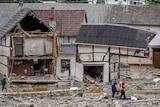Emergency workers walk past flood damage buildings in a Germany village.