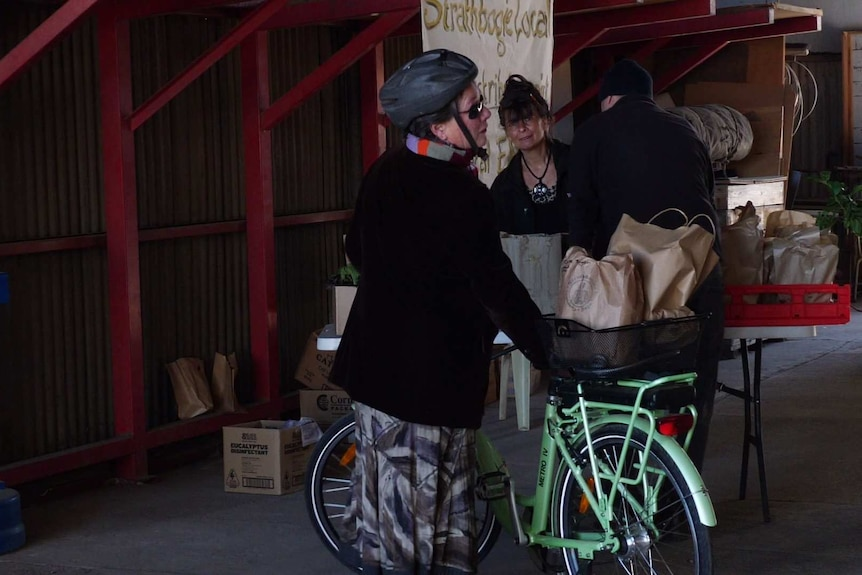 A cyclist picks up a package from an outdoor stall.