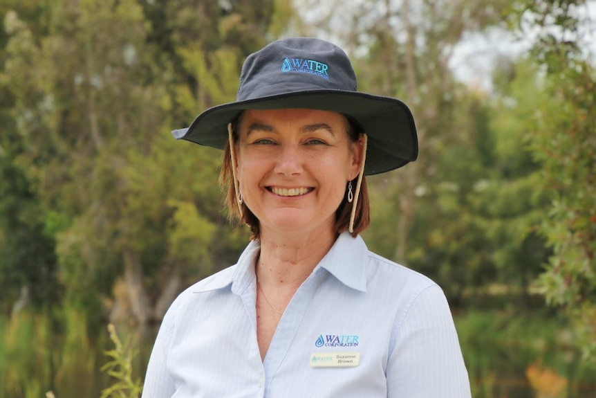 A woman in a navy blue hat and light blue shirt poses for a photo at a park