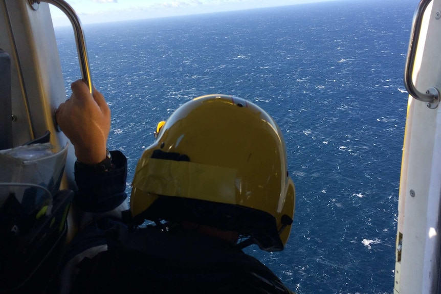 A man in a helmet sits on the edge of a helicopter looking down to sea