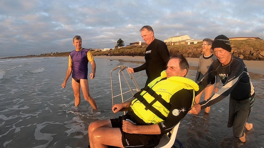 People in bathers laugh with Jim Pevitt as he is pushed into ocean