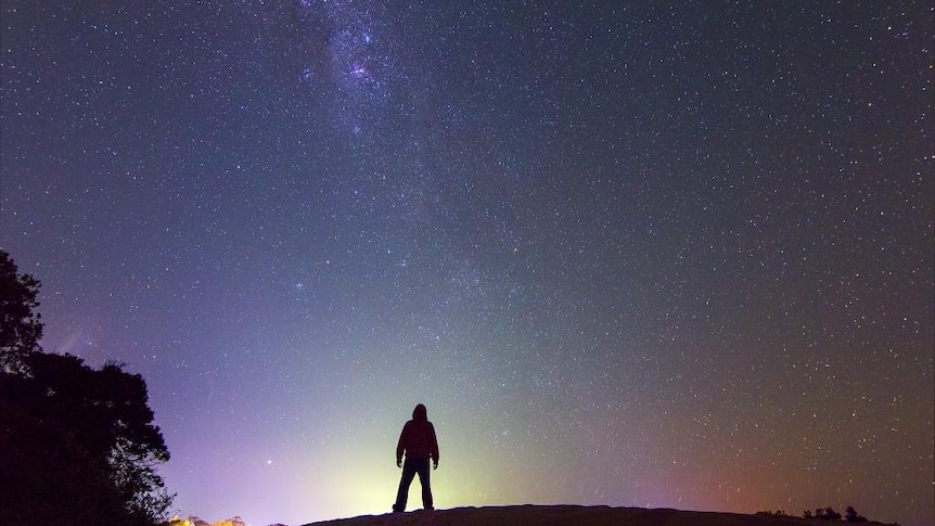 Dylan O'Donnell standing on rock in front of sky full of stars.