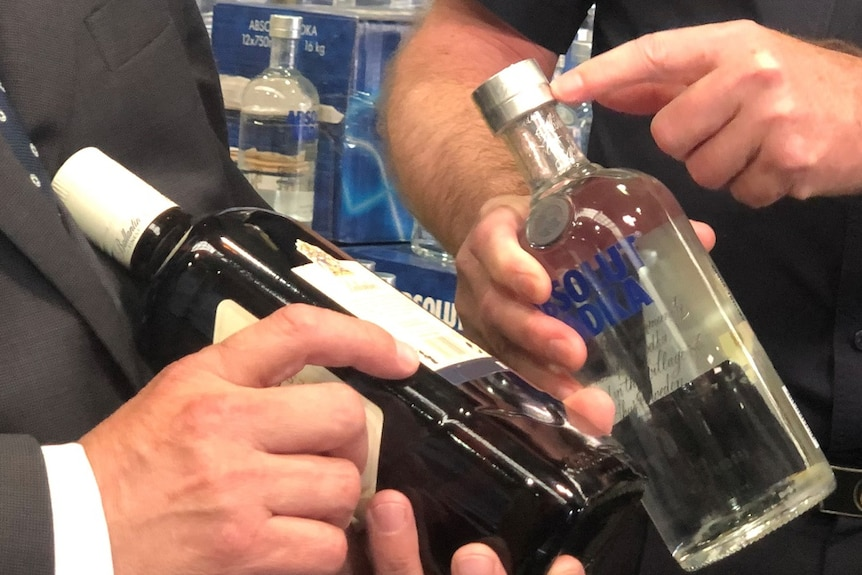 A close-up shot of two men handling bottles of vodka and spirits which have had their labels removed.