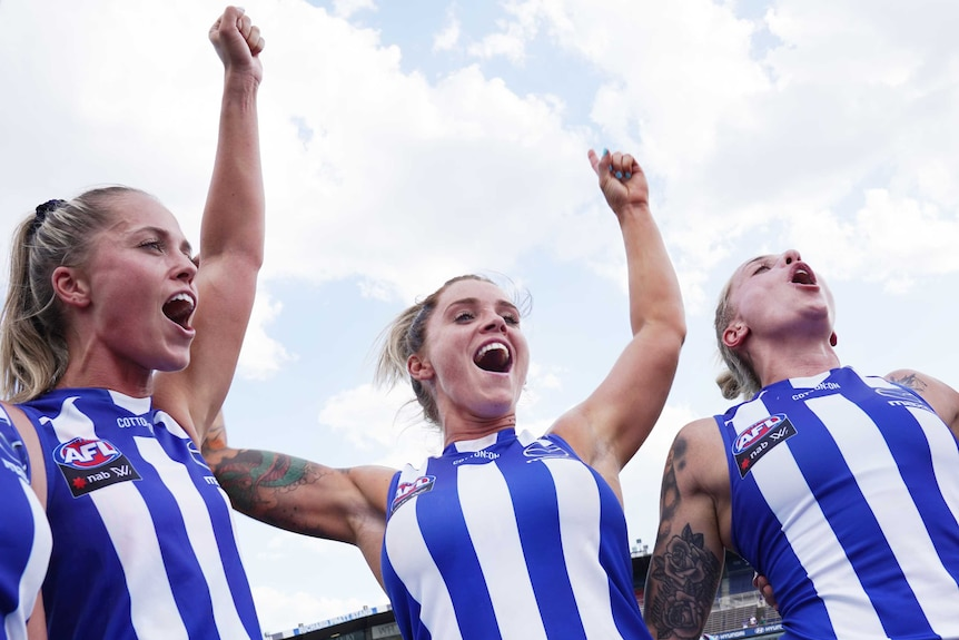 Sophie Abbatangelo, centre, holds both her arms up in the air wearing a blue and while singlet with two players next to her