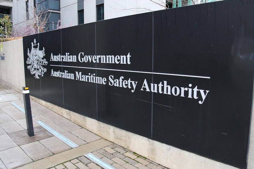 A black sign on a concrete wall that reads 'Australian Government. Australian Maritime Safety Authority'.