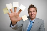 Man in suit holding out hand with small yellow sticky notes stuck to end of each finger