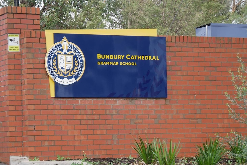A red brick wall with a blue and yellow sign saying Bunbury Cathedral Grammar School