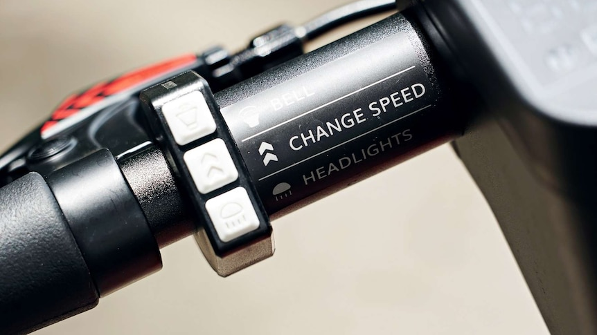 A close-up shot of a Neuron e-scooter handle showing buttons for a bell, headlights and changing speed.