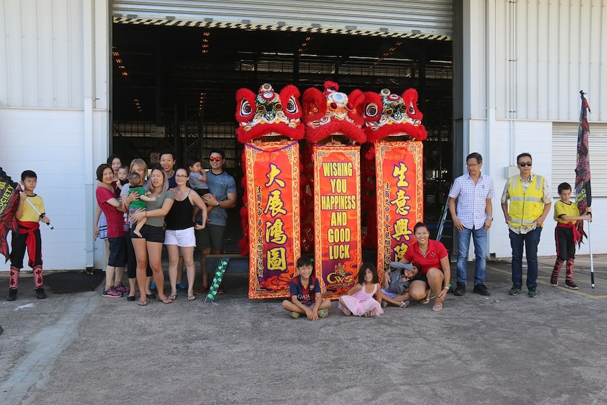 Three Chinese dragons and about 20 people gather outside a warehouse