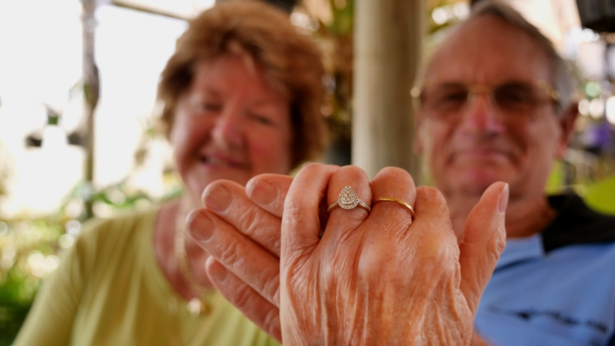 An older woman and an older man sit in a garden, holding up her hand with an engagement ring on it