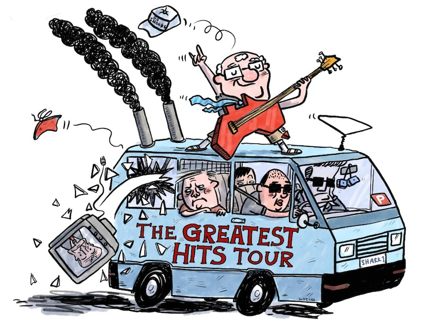 A man plays an electric guitar atop a van marked 'the greatest hits tour'