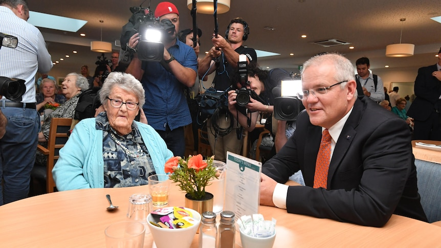 Scott Morrison sits down with a woman in a nursing home surrounded by cameras.