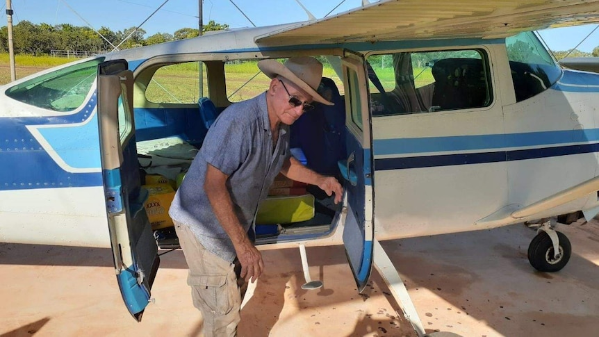 A pilot unloads pizzas from a plane at a remote NT cattle station.