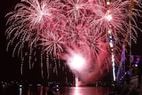 Bright red fireworks light up the dark night sky over water.