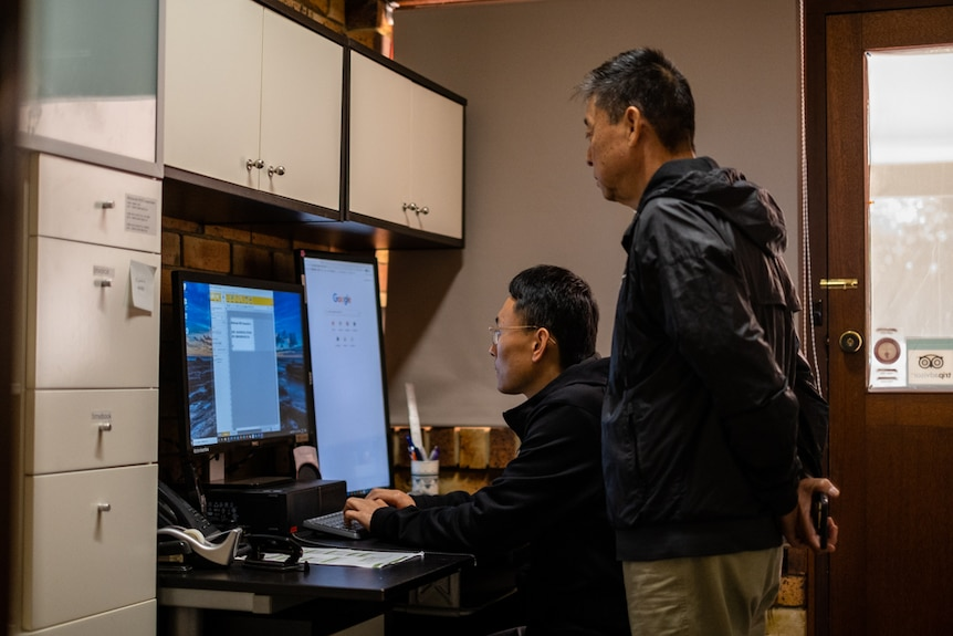 Jason Zhou works on the computer while his father looks over his shoulder.
