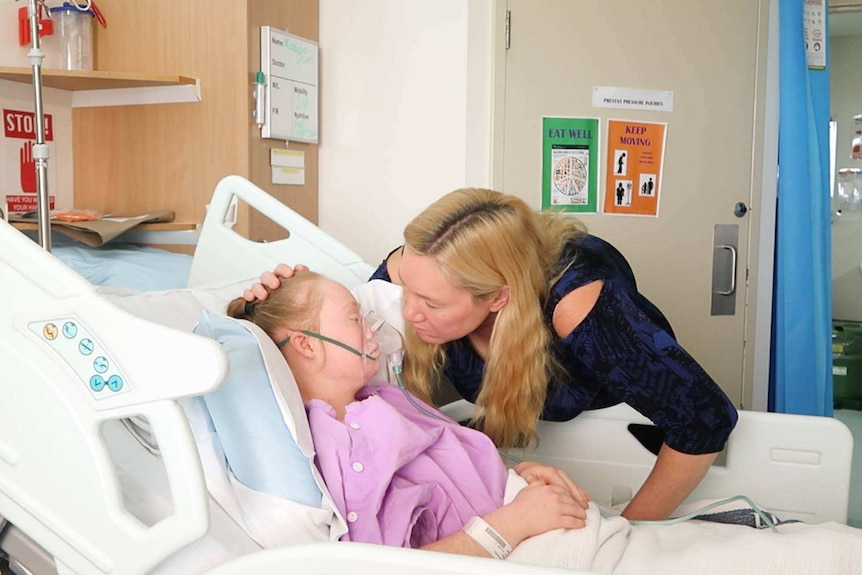 Ms Stuart lays in a hospital bed with an oxygen mask, as a nurse looks on.