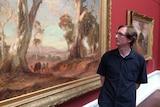 Art history student Ralph Body looks at a hanging Sir Hans Heysen painting.