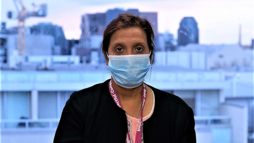 Joy stands wearing a surgical mask, looking to the camera, with a Melbourne city view behind her.