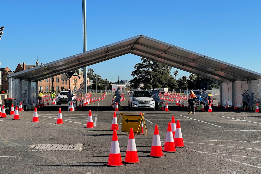 Cars lined up as they drove to a COVID-19 testing clinic under a white marquee