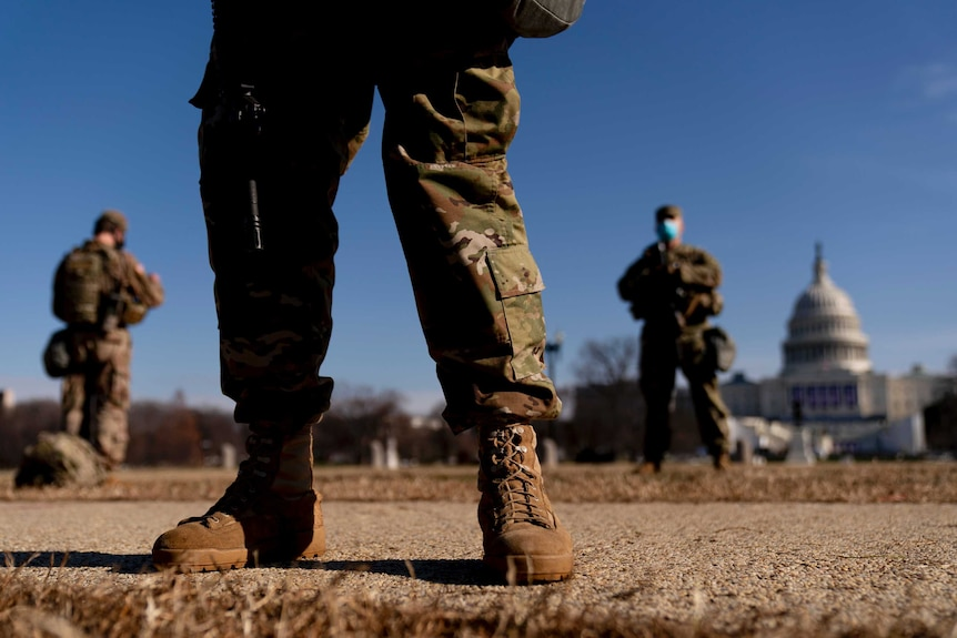 The legs of a person in military clothing in focus, with the US Capitol Building in the background.